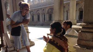 kvinna bugar sig för ett sittande par i indiskt tempel