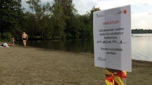 Varningsskylt om maginfluensa vid Kaukajärvis badstrand i Tammerfors.