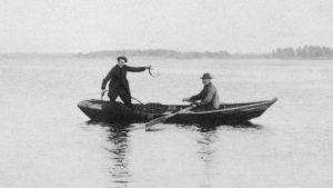 traditionellt nätfiske, två män står i en båt och vittjar nät.
