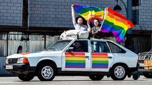 Gayaktivister körde runt i en bil och viftade med regnbågsflaggan.