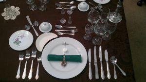 Dukning för 8-rätters middag. Silverbestick, glas och tallrikar.