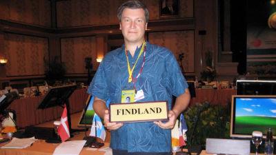 """Stefan står framför ett bord med olika länders flaggor som skymtar i bakgrunden. Han står och ser rakt in i kameran medan han håller i en skylt där det står """"Findland""""."""