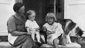 En mor och två barn sitter på en stentrappa.