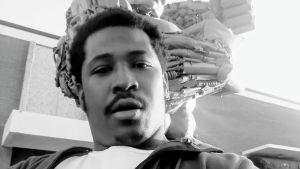 En svartvit selfie på en svart man som ser rakt in i kameran.
