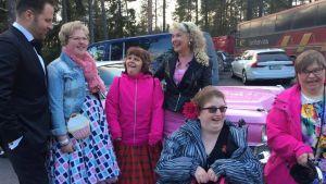 Sångaren Kyösti Mäkimattila i svart smoking i sällskap av ett flertal damer i blommiga klänningar.