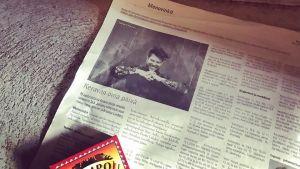 Kuva lehdestä, jossa Samae Koskisen keikkailmoitus. Lehden päällä tulitikut.