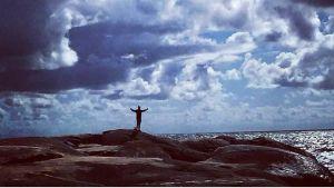 mies rantakalliolla kädet levällään, meri, pilviä