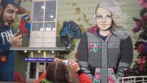 Väggmuraler med en kvinna och en man målade på en tågstations väggar.