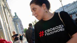 En kvinna står på gatan i svart t-shirt.