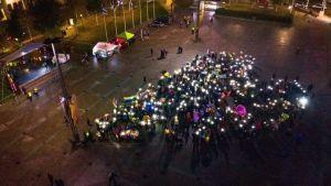 Mikkeli Pride -kulkueen osallistujien muodostama sydän Mikkelin torilla. Osa näyttää valoja muodostelmassa.