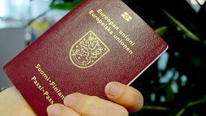 Vinrött finländskt pass med guldtext.