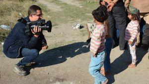 Antti Kuronen på knä med tv-kamera talar med flyktingbarn i Turkiet.