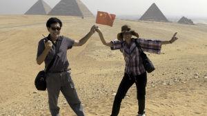 Kinesiska turister poserar framför Gizapyramiderna i Egypten 1.10.2012.