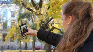 En flicka tar en selfie med sin telefon.