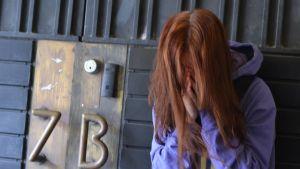 Flicka glömmer huvudet i händerna utanför dörr som det står 7B på