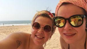 Kvinnor i solglasögon på sandstrad