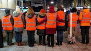 kvinnor i reflexvästar på gata.