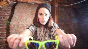 Nainen seisoo tiiliseinän edessä värikkäitä aurinkolaseja kädessä pitäen, kädet ovat ojennettuna eteen kuin pyörän tangolle. Naisella on pipo päässä ja kasvoilla hämmentynyt ilme.