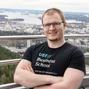 Ung man i svart t-shirt och glasögon står på utsiktsplats, i bakgrunden en stad vid en sjö på långt avstånd.