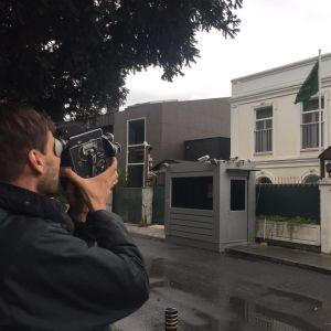 Mies seisoo kadulla ja kuvaa pienellä filmikameralla Saudi-Arabian Istanbulin-suurlähetystön rakennusta. Rakennuksen pihalla on vartiointikoppi ja lippu.