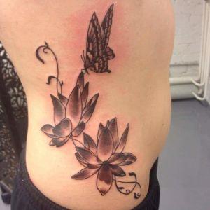 Tatuering som föreställer fjäril och blommor.