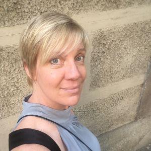 En blond kvinna framför en beige vägg.