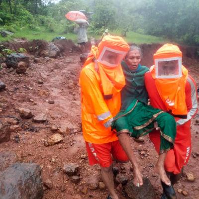 Räddningsarbetare iklädda orangea skyddsjackor bär en kvinna över lermassorna.