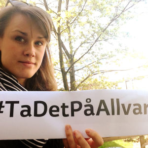 Selfie av Eva-Maria Koskinen med en #TaDetPåAllvar lapp