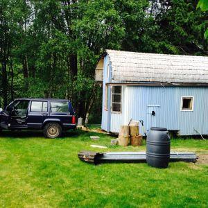 ett blåmålat hus som byggts direkt på botten av en gammal husvagn, sommar