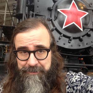 Kalle Kallio katsoo kameraan neuvostoliittolaisen höyryveturin punatähti taustallaan.