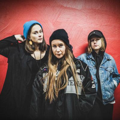 Kolme naista seisoo punaisen seinän edessä kameraan katsoen. Kaikilla ulkovaatteet päällä ja vakavamielisen viileä poseeraus.