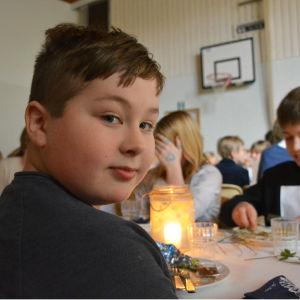 Pojke sitter vid matbord och tittar in i kameran.