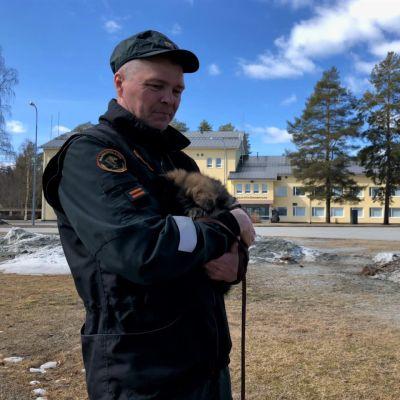 Väiski-pentu on turvassa vanhemman rajavartijan Mikko Hämäläisen sylissä.