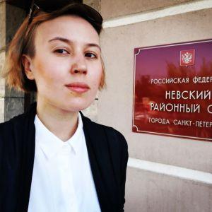 Kvinna i vit skjorta och svart kavaj står vid röd skylt där det står något på ryska.