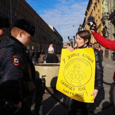 Nainen esittää julistetta venäläisille poliiseille.