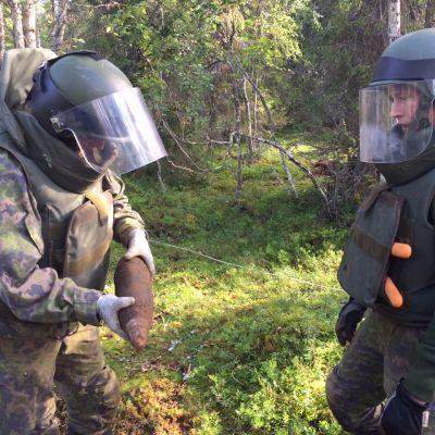 Toisen maailmansodan aikaisia Natsi-Saksan armejan räjähteitä löytyy yhä Lapista. Sodankylän Jääkräprikaatin pioneerit tarkastelevat 105 mm tykinkranaattia  14.8.2015 Pohjois-Lapissa.