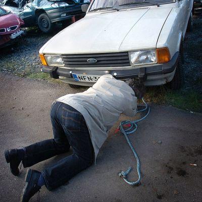 Mies kiinnittää hinausköyttä autoon.