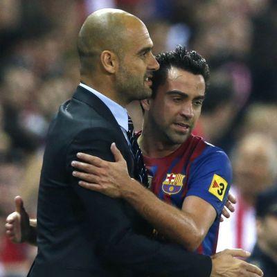 Barcelonan valmentaja Pep Guardiola halaa keskikenttäpelaaja Xavia.
