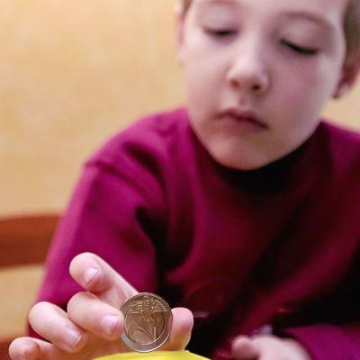 Lapsi laittaa kahden euron kolikon säästöpossuun