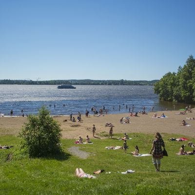 Ihmiset nauttivat auringosta Pyynikin uimarannassa.