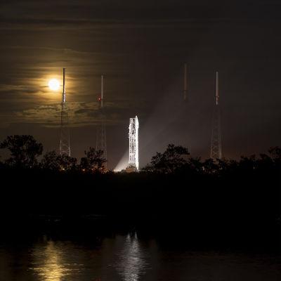 Valaistu raketti pimeällä täysikuun näkyessä taustalla.