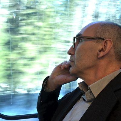 Juha T. Hakala istuu junassa ja tuijottaa ulos ikkunasta.