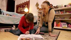 Terhi Heinäsmäki avustaa Amanda-tytärtään koulutehtävien tekemisessä.