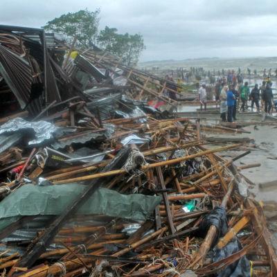 Människor samlas på Pattengastranden som är full av förstörda butiker efter att cyklonen Roanu slagit till mot de sydliga områdena i Bangladesh.