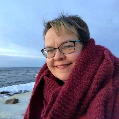 Camilla Cederholm vid havet. Havet är öppet med en liten iskant närmast stranden.