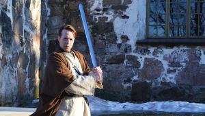En man iklädd kåpa och mantel håller upp ett svärd. Han står framför en stenbyggnad, Sibbo gamla kyrka.