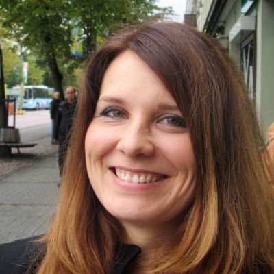 Pirjo Heikkilä hymyilee ja poseeraa Lahden Aleksanterinkadulla.