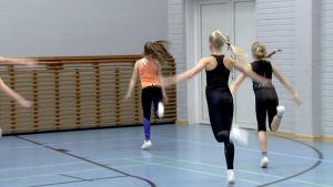 Tytöt harjoittelevat salissa aerobiciä.