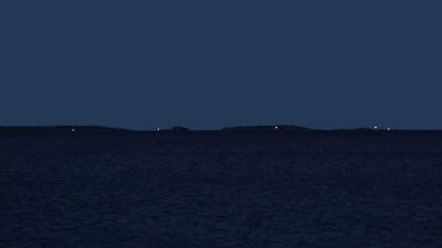 Nattlig vy över havet med blinkande fyrljus.