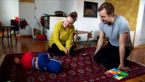 Teemu Syrjälä ja Ulla-Maija Takkunen katselevat lattialla makaavaa poikaansa.